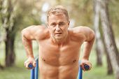 Outdoor Shot Of Athletic Muscular Male Does Pull Ups On Handle Bar, Has Strong Motivation, Wants To  poster