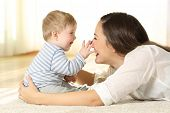 Affectionate Mother And Baby Playing Together On A Carpet On The Floor At Home poster