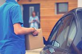 Delivery man in blue uniform delivering parcel box to recipient - courier service concept. Delivery  poster