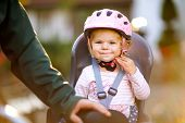 Portrait Of Little Toddler Girl With Security Helmet On The Head Sitting In Bike Seat And Her Father poster