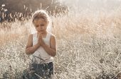 Little Girl Closed Her Eyes, Praying Outdoors, Hands Folded In Prayer Concept For Faith, Spiritualit poster