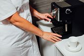 Nurse In Cosmetic Beauty Parlour Making Coffee In Her Tiny Kitchen poster