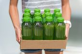 Green smoothie juice bottles box of cold pressed vegetable juices. Woman holding delivery box. Healt poster