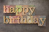 happy birthday - text in vintage letterpress printing blocks against a grunge metal sheet