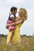 stock photo of family fun  - A beautiful blond haired blue eyed young woman having fun in a field of long grass with her mixed race young daughter - JPG