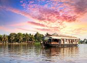 pic of houseboats  - House boat in backwaters near palms at dramatic sunset sky in alappuzha Kerala India - JPG