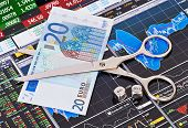 Scissors Cutting  Euro  Banknote, Dices Cubes With The Words Sell Buy. Financial Charts And Columns