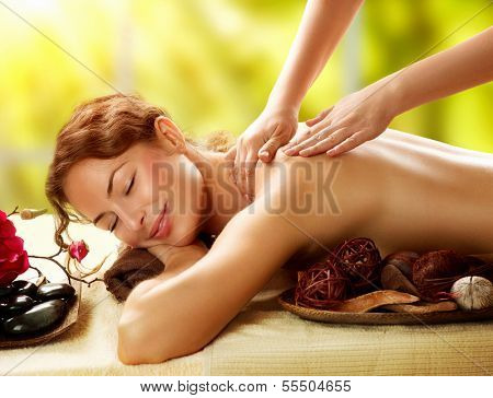 Spa. Beautiful Woman in Spa Salon getting Massage. Healthy massage of body in spa salon. Beauty trea poster