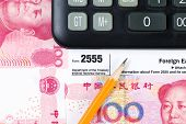 foto of irs  - Horizontal photo of partial IRS Income tax form 2555 for Foreign Earnings from outside the United States pencil and calculator with Chinese Currency in background - JPG