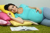 Young pregnant woman lying on floor and reading book on wall background