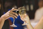 Close up of two women's hands toasting with wine glasses