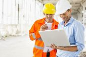 image of headgear  - Male architects using laptop at construction site - JPG