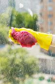 stock photo of soapy  - hand in yellow rubber glove washing window glass by soapy water - JPG