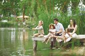 stock photo of little kids  - Young happy family with kids fishing in pond in summer - JPG