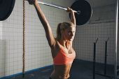 image of bodybuilder  - Strong woman lifting barbell as a part of crossfit exercise routine. Fit young woman lifting heavy weights at gym.
