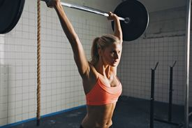 stock photo of heavy  - Strong woman lifting barbell as a part of exercise routine - JPG