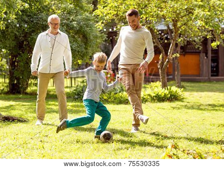 family, happiness, generation, home and people concept - happy family playing football in front of h
