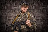 picture of cap gun  - Soldier with a gun in hand on the brick wall background - JPG