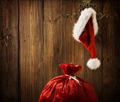 stock photo of santa claus hat  - Christmas Santa Claus Hat Hanging On Wood Wall Xmas Concept Decoration Over Grunge Wooden Background - JPG