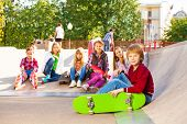 picture of skateboarding  - Blond boy with skateboard and his mates sitting in a row behind on the ground during sunny day at children park for skateboarders