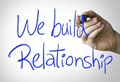 image of courtesy  - We build relationship hand writing on blue marker on transparent wipe board - JPG