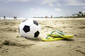 foto of ipanema  - Soccer ball and a yellow Flip flop on the beach - JPG