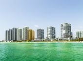 stock photo of jade blue  - Beautiful Jade Beach in sunny isles beach with blue sky and skyscraper - JPG