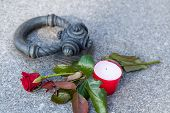 pic of graveyard  - Close up of tombstone with single rose and candle on the graveyard