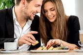 picture of cheesecake  - Young couple smiling and eating cheesecakes at the restaurant  - JPG