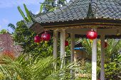 picture of gazebo  - Azian Gazebo under Blue Sly and Beautiful Flowers - JPG