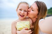 picture of daughter  - Happy family mother and her adorable little daughter at beach making selfie - JPG