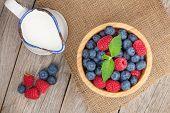 stock photo of jug  - Blueberries and raspberries bowl and milk jug on wooden table - JPG