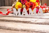 picture of bunch roses  - Bunch of roses with a gift box and word Mama on wooden background - JPG