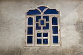 picture of punjabi  - a blue timber framed traditional punjabi window set in a rendered wall of a building in a Bishnoi village - JPG
