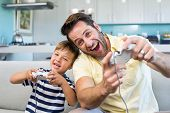 stock photo of indoor games  - Father and son playing video games together at home in the living room - JPG