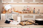 stock photo of chefs hat  - Little cute girl with chef hat preparing cookies - JPG
