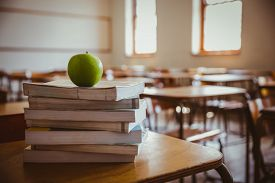 stock photo of piles  - Apple on pile of books at the elementary school - JPG