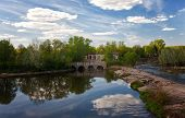 picture of dam  - Summer landscape with a dam through the river and fishermen in a sunny day - JPG