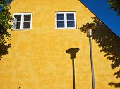 stock photo of lamp post  - Lamp Post Street Road Light Pole casting a shadow over a yellow house - JPG