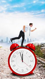 stock photo of running-late  - Geeky businessman running late against stony path leading to misty cityscape - JPG