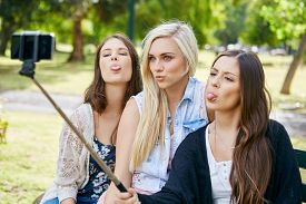 foto of sitting a bench  - young happy girl friends sitting on park bench taking selflie photos with mobile cell phone on stick - JPG
