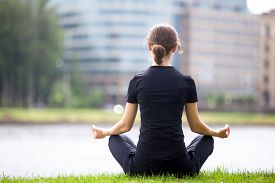 pic of pranayama  - Young woman sitting cross legged on river bank in front of blue glass modern office building meditating practicing yoga Easy Pose Sukhasana asana for meditation pranayama breathing back view - JPG