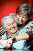 image of elderly woman  - Daughter hugs her senior mother and smiles - JPG