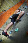 stock photo of climbing wall  - Young man climbing indoor wall - JPG