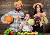 Harvest Festival Concept. Parents And Daughter Celebrate Harvest Holiday Pumpkin Vegetables Fruits.  poster