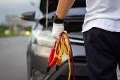 Car Mechanic Man Holding Battery Jumper Cables To Charge A Dead Battery. Close Up Hand Charging Car  poster