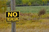 An Image Of A Black And Yellow No Trespassing Sign Posted To An Old Wooden Post. poster