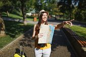 Young Smiling Traveler Tourist Woman In Casual Clothes Hat With Suitcase City Map Pointing Index Fin poster