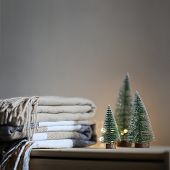 Stack Of Beige Checkered Wool Blankets And Two Christmas Trees On A Wooden Chest. Cozy Winter Still poster