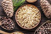 Pine nuts in the bowl and pine nut cones on the wooden table. Organic food. Top view. poster
